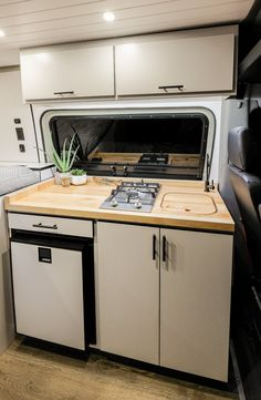 JOMOVAN'S kitchenette is equipped with an Isotherm 85 Elegance refrigerator, two burner cook top, a high capacity water filtration system, and a jet black filtered drinking faucet to match the modern aesthetic. Camper Diy, Bus Camper, Cargo Trailer Camper, Transit Camper, Sprinter Camper, Van Conversion Interior, Camper Van Conversion Diy, Van Conversion High Top, Caravan Makeover