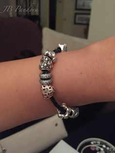 Pandora 2016 Club charm and Pandora Rose heart on black leather bracelet.
