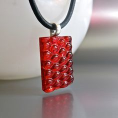 """Simplicity at its best. Beautiful Hand Made Fused Glass Necklace. The texture of the glass gives the Transparent Red Glass depth and playfulness. Truly unique yet simple.  Perfect holiday accessory for a casual party or a stylish gift to your special friend.    Size of the pendant is 1 3/4 1 1/4 ( 2cm x 3cm)    It comes with a 18"""" (46cm) black leather cord."""