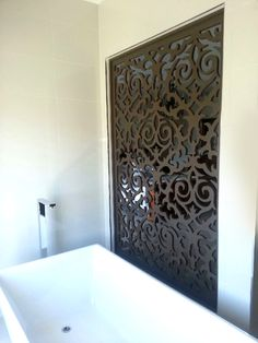 Modern bathroom with a decorative screen installation. QAQ screens can add warmth to an otherwise clinical modern bathroom. This is the exotic, baroque, 'Morocco' screen design.
