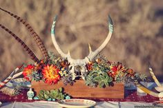 Succulents, painted antlers & feathers. Striking centerpiece by http://primarypetals.com   Photo by http://lukasvandyke.com