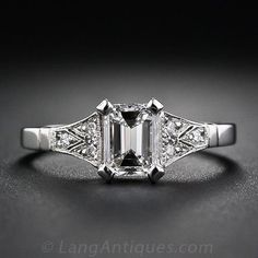 An ice-white, high-quality emerald-cut diamond, weighing .90 carat, E color, VS1 clarity, radiates from atop an elegantly restrained Art Deco style mounting, crafted in platinum with tiny full-cut diamonds. A stunning and stately vintage style engagement ring. Ring size 6 1/2.