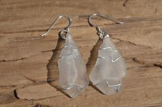 Genuine frosted white sea glass sterling silver hand wire wrapped earrings. The wire wrapped sea glass is hung on a pair sterling silver french