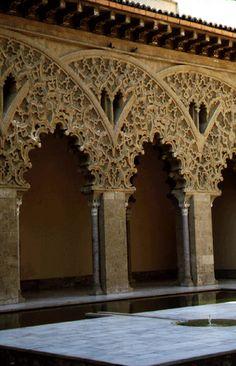 """""""El entrelazado de arcos con función estrictamente decorativa es frecuente en el arte árabe. En el caso de la Aljafería llega este uso a su maestría extremada en la decoración. Los arcos primarios sostenidos por pilares y esbeltas columnas se combinan por pares formando amplias curvas que cobijan una repetición diminuta de los primarios."""" Esta obra y muchas otras del palacio fueron parte de la reconstrucción hecha por los reyes árabes de Zaragoza entre 1030 y 1081 (siglo XI)."""