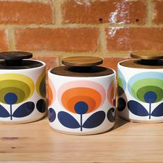 Orla Kiely 1 litre storage jar with yellow seventies style flower heads. Part of the 70s oval flower range. Fitted with a wooden lid