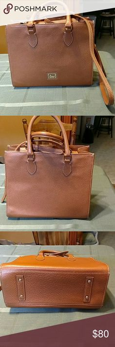 Authentic Dooney and Bourke Cross Body! Pebble grain leather, beautiful caramel brown color, mint condition. Cross body strap can be detached to carry bag as a satchel. Gold hardware, 4 gold metal feet on bottom, zippered compartment and three slots inside, leather key fob, pink interior, **has Dooney tag with serial # inside but hard to get a picture**. This bag is perfect for career or casual and goes with everything! Classic and gorgeous! Dooney & Bourke Bags Crossbody Bags