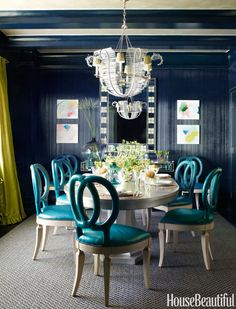 Walls in the glamorous dining room are clad in Phillip Jeffries's Lacquered Strié, and the trim is painted in a high-gloss blue.