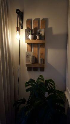 Koperen hanglamp bij pallet aan de muur..