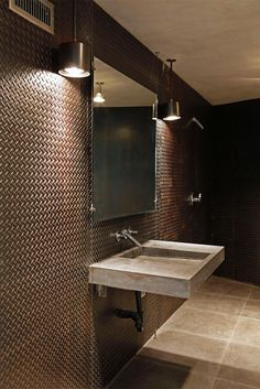 The guest bathroom features walls lined in blackened steel diamond plate, cement tile floors and a cement floating sink designed by Andrea Michaelson. The open shower creates a spacious feel. The contemporary design style with industrial modern touches carries throughout the home.