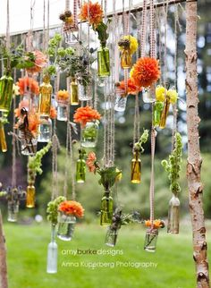 Hanging salvaged bottles and jars on chuppah at wedding ceremony.