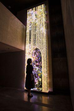 高さ5210mm、横幅1280mm、奥行き160mmのLEDでできた巨大な立体物である。   月ごとに変化しながら、一年を通して、徳島に咲く花々が咲いては散り、変化していく。  花は生まれ、成長し、つぼみをつけ、花を咲かせ、やがて散り、枯れて死んでいく。つまり、花は誕生と死滅を、永遠に繰り返し続ける。    流れ落ちる砂の前に人が立つと、砂はその人がつくる存在感に衝突し、砂が割れていく。 古代から、人々は、落下していく砂を見て、短い時間の概念を知り、そして、咲く花々の変化で、長い時間の移り変わりを感じてきた。   作品はコンピュータプログラムによってリアルタイムで描かれ続けている。あらかじめ記録された映像を再生しているわけではない。全体として以前の状態が複製されることなく、鑑賞者のふるまいの影響を受けながら、変容し続ける。今この瞬間の絵は二度と見ることができない。