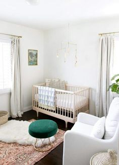 Nursery envy! Simple wood crib with stunning rug and ottoman.