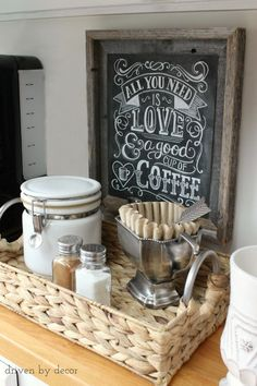 A simple DIY home coffee station with chalkboard print art and a canister for coffee along with a trophy cup holding coffee filters all corralled in a woven tray from HomeGoods (sponsored pin)
