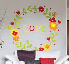 A beautiful floral wreath made up of bright spring colours to decorate your home and spread some love! Create warm and loving atmospheres in any room and freshen up your walls. #Love #Decoration #Floral