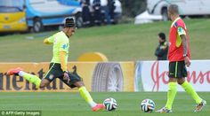 Shooting practice: Neymar aims for goal as team-mate Dani Alves watches on during training on Saturday
