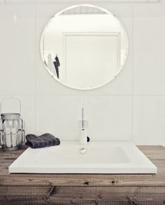 Love the simplicity of the round mirror in the minimalist bathroom
