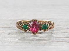Vintage Victorian ring made in 18k yellow gold. Set with two emeralds and centered with rubellite. Circa 1880.