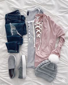 gray and blush winter outfit. ripped jeans, lace up blush sweater, gray sneakers, gray knit pom hat