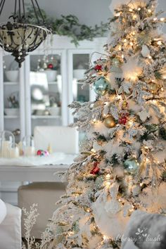 "The flocked tree – secret garland revealed  ""I drove to the Dollar Store and bought the entire display of white dusters. We took them apart and simply inserted them into the crevices and gaps in between the branches."""