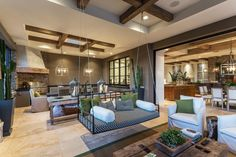 General contractor Emilio LoCascio suspended a swing from the ceiling to add an element of fun and whimsy to this eclectic living area, which opens up to the dining room and kitchen. Exposed beams, matching square chandeliers and beautiful tile floors are used throughout all the spaces to create a seamless look.