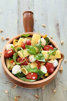 healthy lunch: pasta salad with tomatoes, mozzarella, basil and arugula