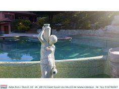 Piscina de FERRÓN@PISCINAS. Detalle de una fuente con figura de mujer y sus cántaros. Nivel desbordante, borde simulando la piedra.