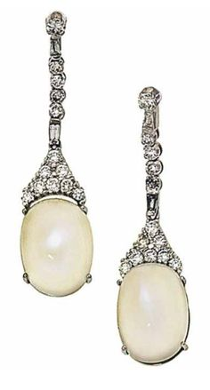 A pair of moonstone and diamond earpendants   Each oval cabochon moonstone drop and brilliant-cut diamond cluster surmount to a brilliant and baguette-cut diamond line suspension, mounted in 18ct white gold, post fittings, London hallmark, 4.7cm long