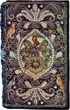 Embroidered book with pearls and parrot images. Center medallion appears to be a swordsman fighting an octopus/kraken. [Source unknown] Photo enhanced to show detail.