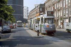Amsterdam, 1972. Aardgas heeft het stadsgas vervangen, maar de Van Hallstraat wordt nog gedomineerd door de gashouder van de Westergasfabiek. De GVB-tram en NZH-bus (van IJmuiden naar Amsterdam Marnixstraat) zijn allebei Werkspoor-producten