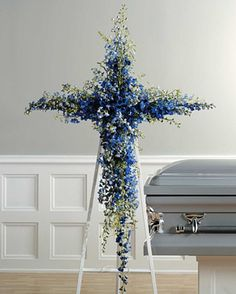 Beautiful floral cross funeral arrangement made using blue delphinium. Perfect for his funeral or memorial service. Church Flowers, Funeral Flowers, Wedding Flowers, Casket Flowers, Flowers Wallpaper, Wallpaper Art, Funeral Floral Arrangements, Funeral Sprays, Cemetery Decorations