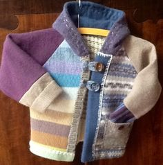 Hoodie Sweater reconstructed from several upcycled wool sweaters. This is a cozy sweater jacket for crisp fall days, toddler size 2T. Soft and dusty shades of blue, purple, cream and tan make this a fun jacket for many outfits. Two button closure and the cozy hood is lined with cashmere.    Hand wash, lay flat to dry.