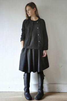 Jeanne porte : - un gilet uniforme en maille grise  - une blouse uniforme en lin noir  - une jupe uniforme en lainage gris
