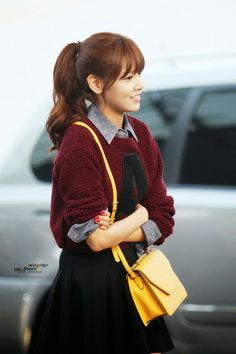 Maroon sweater with black skirt and yellow leather hand bag