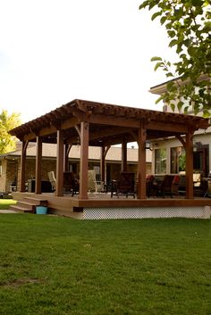 DIY timber frame ShadeScape™ pergola kit installed for shade over solid wood deck in backyard. The pergola features a full wrap latticed roof with decorative metal candle lanterns and power post with light switches, plugs and string lights.