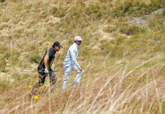 Phil Mickelson (left) and Rickie Fowler walk to the 13th hole during a ...