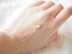 I made this delicate slave bracelet with very dainty 14k gold-filled chain. This hand chain is so beautiful, simple and dainty.  The bracelet closes with a gold filled plated spring clasp.    Bracelet features:  14k gold filled chain   gold plated bezel with Swarovski white oparl set measures 4mm    Size: Msize ring 2.75inc,ring to bracelet 3inc,bracelet 6inc   Lsize ring 2.75inc,ring to bracelet 3.25inc,bracelet 6.5inc    *Please let me know if your hand measurements deviate from this and I…