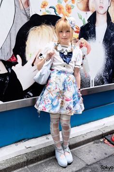 """Sakuraco:  Her look features a beautiful undersea-print skirt (the official title of the print is """"Mermaid"""") from the Harajuku brand Milk, a white top (with a sailor collar, bow tie, and lace), ribbon print tights from Candy Stripper, and power blue studded wedges with musical notes. Accessories include a cute straw hat with a bunny attached (the bunny has a polka dot bow tie!), and a blue Milk Harajuku bag with a bow and hearts."""