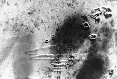 Overhead view of a South African Air Force raid on the German airfield at Martuba Libya 6 July 1942. Note circular dust patterns of bomb bursts and lines of dust kicked up by scrambling aircraft.