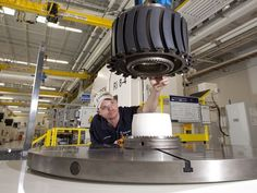 Rolls-Royce employee Jody Driggers checks the measurement of a fan disc for an aircraft engine at the company's Prince George, Va. factory