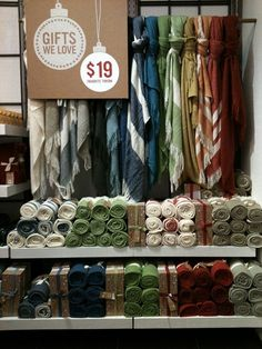 Display idea for scarfs at a craft show. Display scarves behind table with signage and roll or fold stock in front