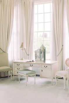 light and airy bridal suite with big bay windows, white aesthetic in the room and french antique dresser and chair with three fold mirror