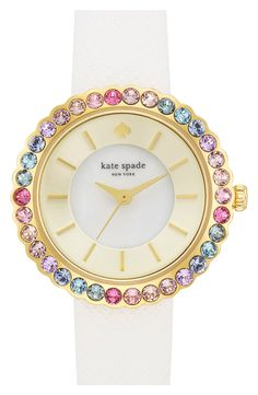 Colorful sparkling crystals nestle in the scalloped round case of this pretty Kate Spade watch.