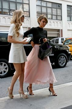 Jessica Alba wears a long pink skirt and a black sweater as she heads into a building in New York City