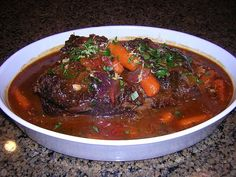 Boliche Cubano (Cuban Pot Roast) ~ a special Cuban meal would not be complete without Boliche. The beef (most commonly eye of round roast), is marinated in the tangy Cuban marinade, Mojo Criollo, then stuffed with chorizo, and cooked in a flavorful wine broth until the beef is meltingly tender. Potatoes, carrots and olives are often added to the broth for an extra hearty touch. #Cuba #Food #Pot_Roast #Boliche