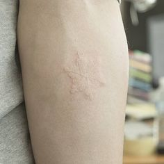Tatuaje de un pequeño copo de nieve situado en el... - Pequeños Tatuajes para Mujeres y Hombres