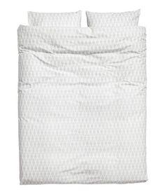 Hvit. Et dobbelt sengesett i fintrådet bomullskvalitet med trykt mønster. Dynetrekket har skjulte trykk-knapper nederst i metall. To putevar. 30s-garn.