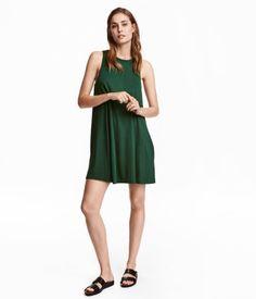 Olivgrün. Ärmelloses Jerseykleid in A-Linie. Oben doppellagig gearbeitetes Modell mit etwas tieferen Ärmelöffnungen und Taschen in den Seitennähten.