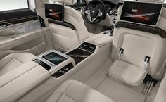 BMW 7 Series Sedan  The BMW 750i xDrive Rear Executive Lounge featuring a folding table in exclusive White Ivory Nappa leather and Dark Grey Poplar wood trim.