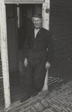 Man in Volendammer streekdracht. Hij draagt een 'Schokker broek' en een 'blempie' (jas). Dit model broek werd aan het eind van de 19de eeuw nog algemeen gedragen, maar op het moment dat de opname gemaakt werd (1946) was deze broek reeds uit de mode. #NoordHolland #Volendam