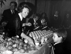 Koningin Beatrix schenkt op 22 december 1980 in het Paleis op de Dam in Amsterdam een kopje chocolademelk in voor haar neefje prins Floris. De prinsen Johan Friso en Constantijn helpen mee en prins Claus kijkt op de achtergrond toe.